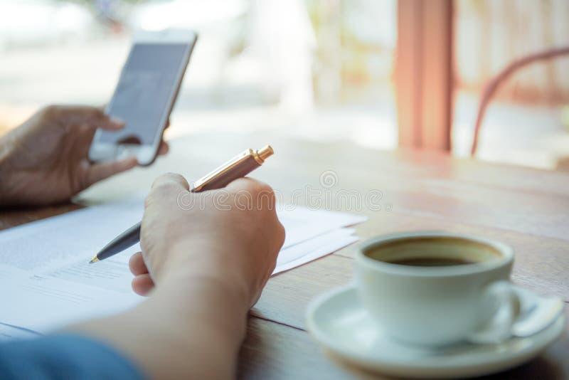 Affärsmän räcker läsningdokument för hållande penna och mobiltelefon royaltyfri fotografi