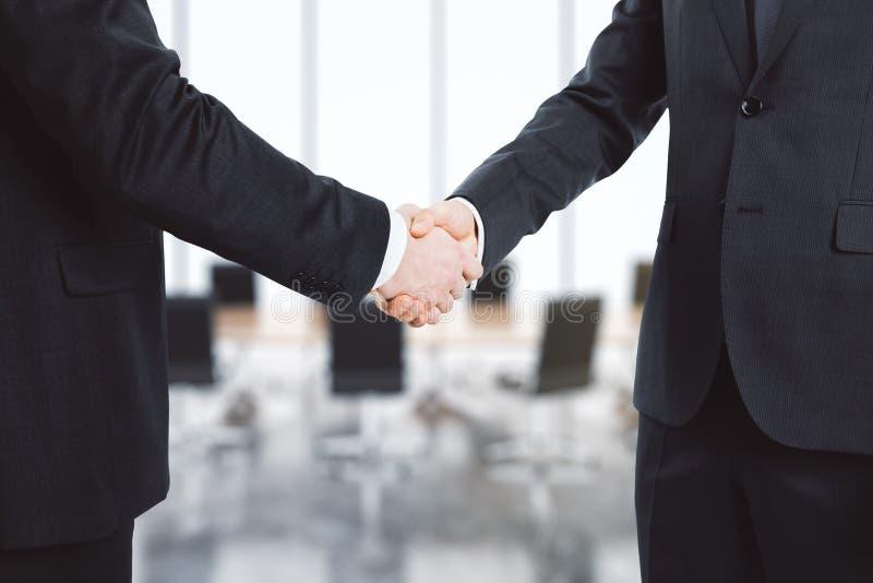 Affärsmän skakar deras händer i konferensrum arkivfoto