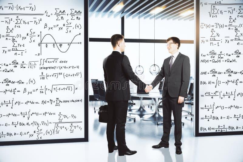 Affärsmän skakar händer i kontoret med väggar med likställande royaltyfria foton