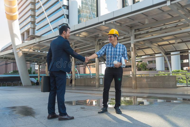Affärsmän skakar händer med en ung tekniker i staden royaltyfri bild