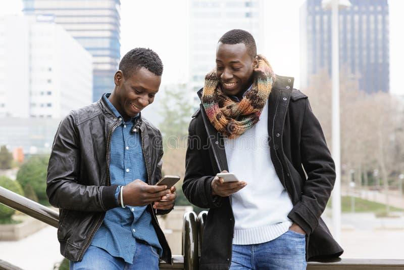 Affärsmän som använder mobilen i gatan fotografering för bildbyråer