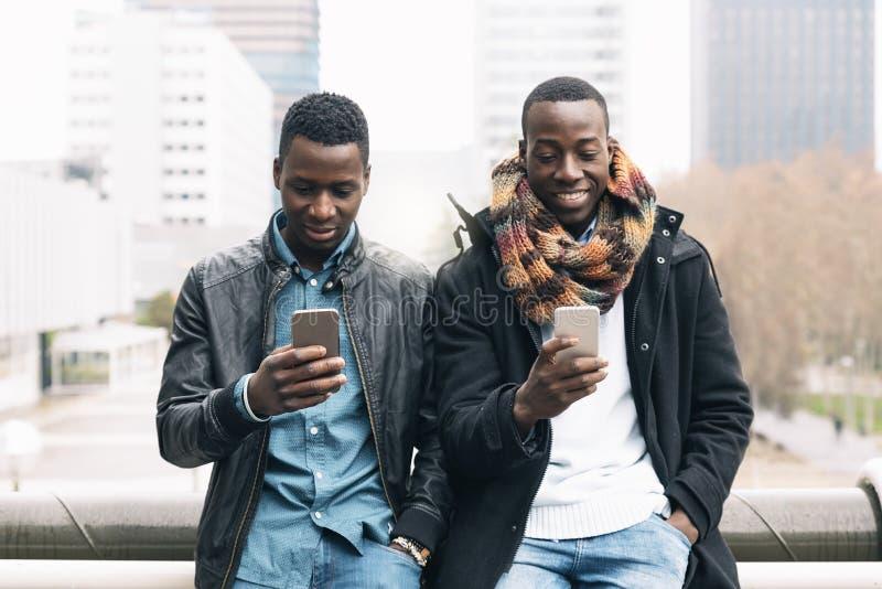 Affärsmän som använder mobilen i gatan royaltyfri foto