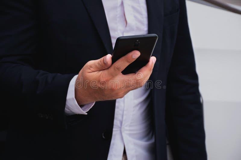 Affärsmän som bär en svart dräkt, rymmer mobiltelefoner arkivbilder