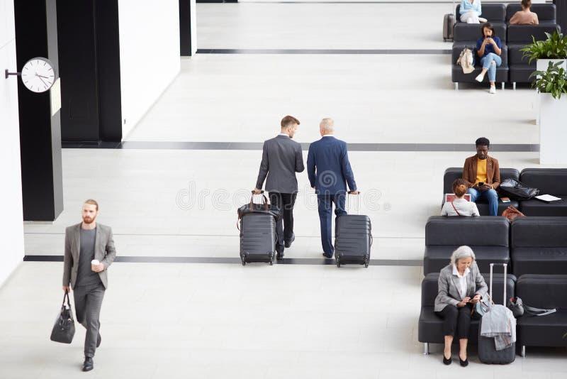 Affärsmän som bär rullade resväskor i flygplats arkivfoton
