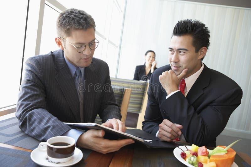 Affärsmän som diskuterar avtalet i restaurang royaltyfri fotografi