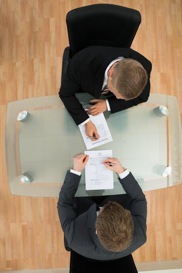 Affärsmän som fyller ansökningsblanketten royaltyfri foto