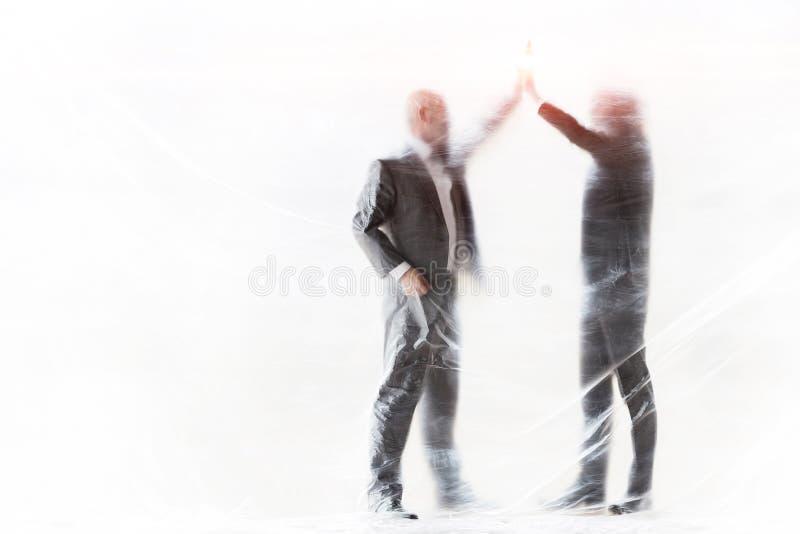 Affärsmän som ger varandra höga fem gånger medan de är täckta med plast för att skydda sig mot Coronavirus royaltyfria bilder