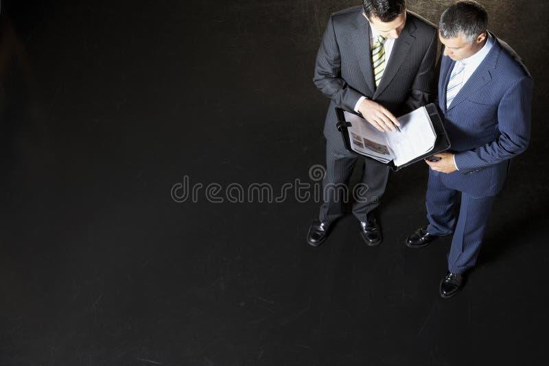 Affärsmän som granskar dokument arkivbilder