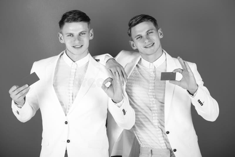 Affärsmän som ler i vita omslag på blå bakgrund royaltyfri bild