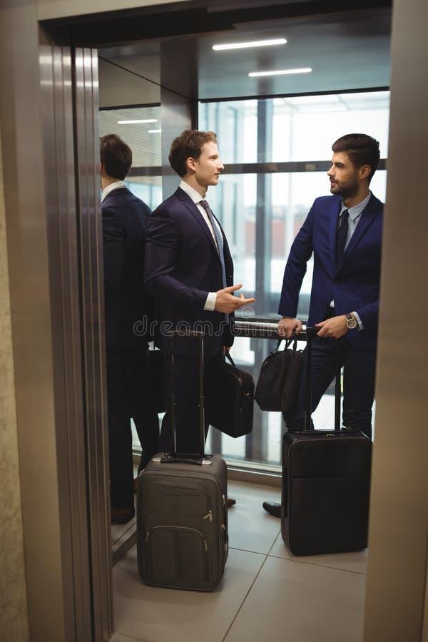 Affärsmän som påverkar varandra med de i hiss royaltyfria bilder