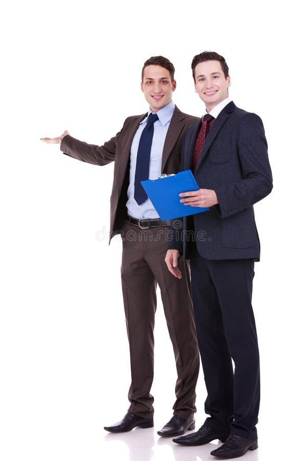 affärsmän som presenterar två barn royaltyfria bilder