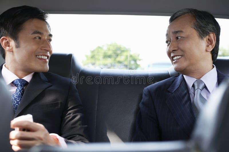 Affärsmän som samtalar i Backseat arkivfoton