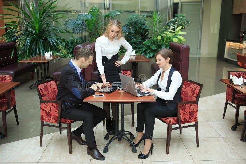 Affärsmän som sitter i kafét för en bärbar dator arkivbild