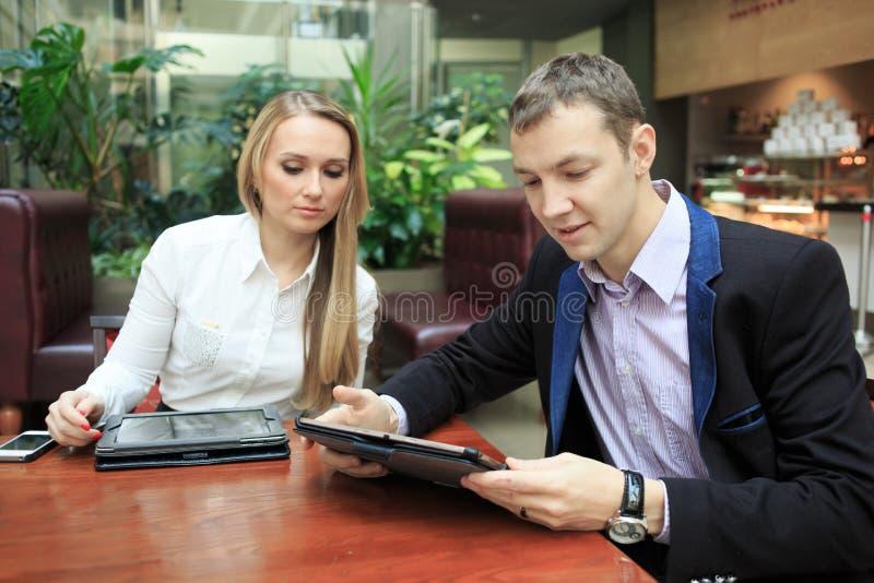 Affärsmän som sitter i kafét för en bärbar dator flickor två fotografering för bildbyråer