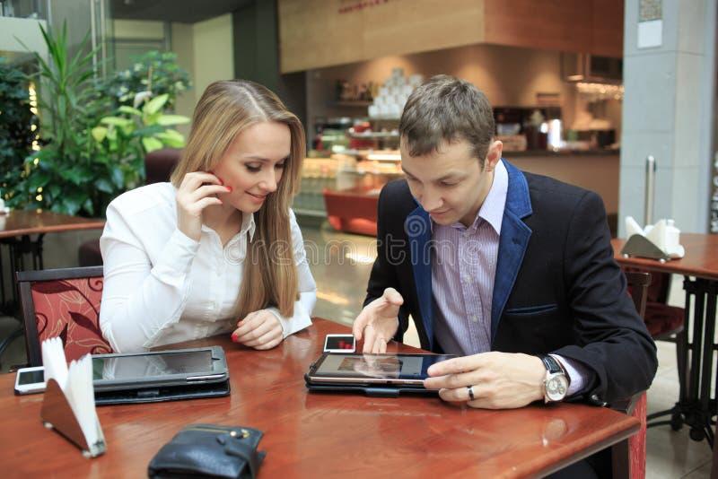 Affärsmän som sitter i kafét för en bärbar dator flickor två arkivbild