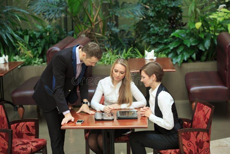 Affärsmän som sitter i kafét för en bärbar dator flickor två royaltyfria bilder