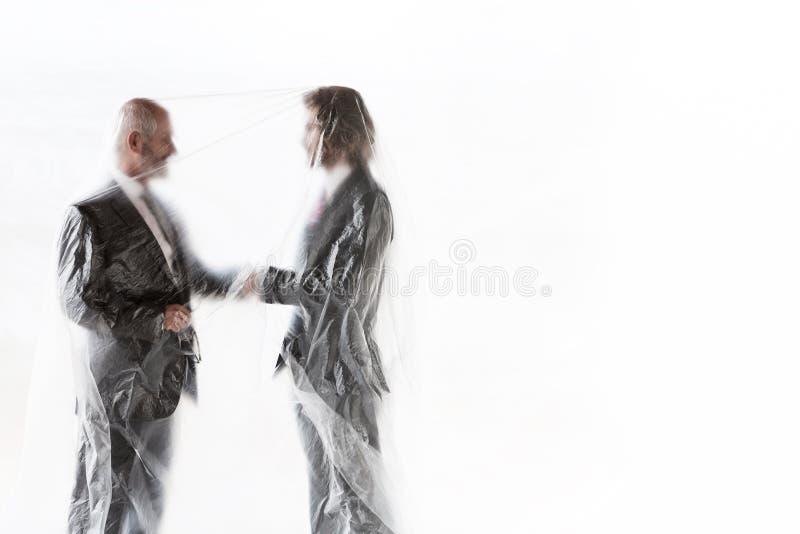Affärsmän som skakar hand och som är täckta med plast för att skydda sig mot Coronavirus royaltyfri foto