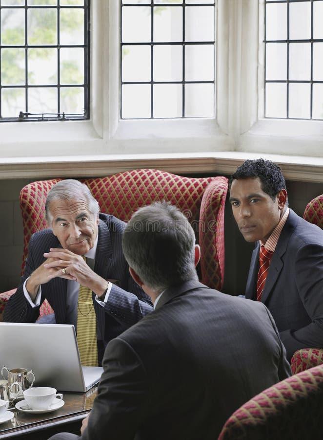 Affärsmän som talar över bärbara datorn i lobby royaltyfri bild