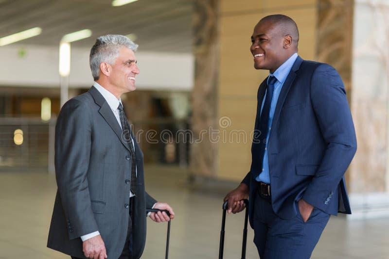 Affärsmän som talar flygplatsen arkivbild