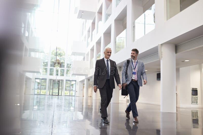 Affärsmän som talar, som de går till och med kontorslobby royaltyfri bild