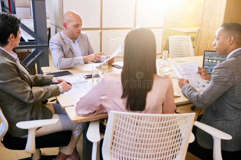 Affärsmöte mellan fyra yrkesmässiga företagsamma ledare inomhus royaltyfri fotografi