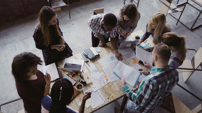 Affärsmöte på det moderna kontoret Bästa sikt av den blandras- grupp människor som tillsammans arbetar nära tabellen arkivfoton
