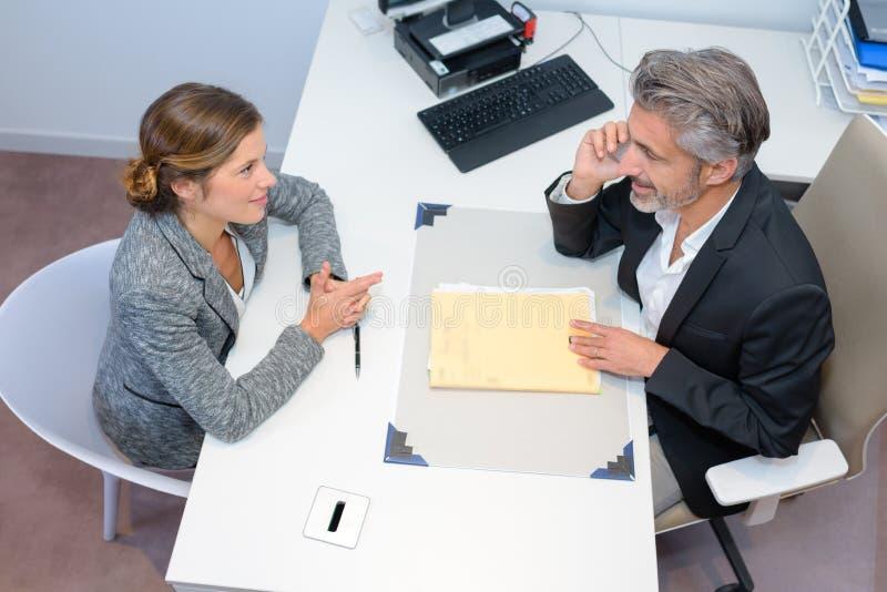 Affärsmöte som i regeringsställning diskuterar dokument arkivfoto