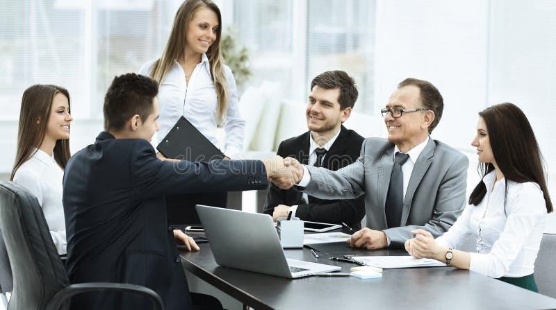 Affärsmöte tabellen och handskakningen av affärspartners royaltyfria bilder