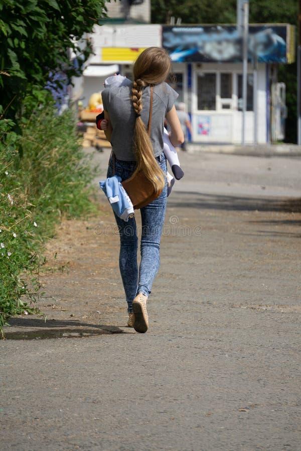 Affärsmamma som arbetar med ett barn i hennes armar arkivfoto