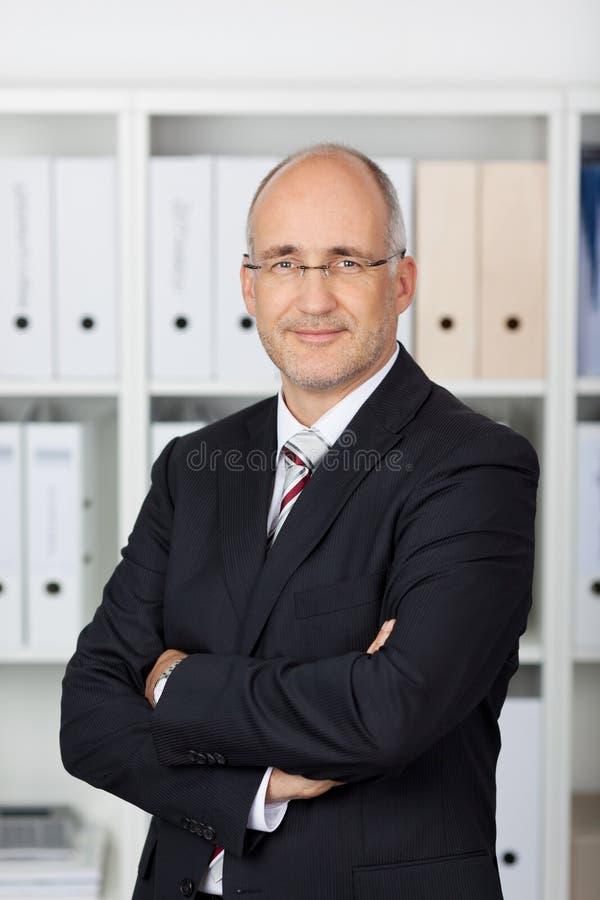 Affärsman With Arms Crossed som i regeringsställning står royaltyfri bild