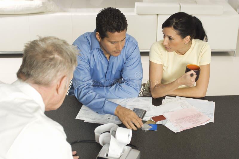 Affärsman Assisting Couple med kreditkortar arkivfoto