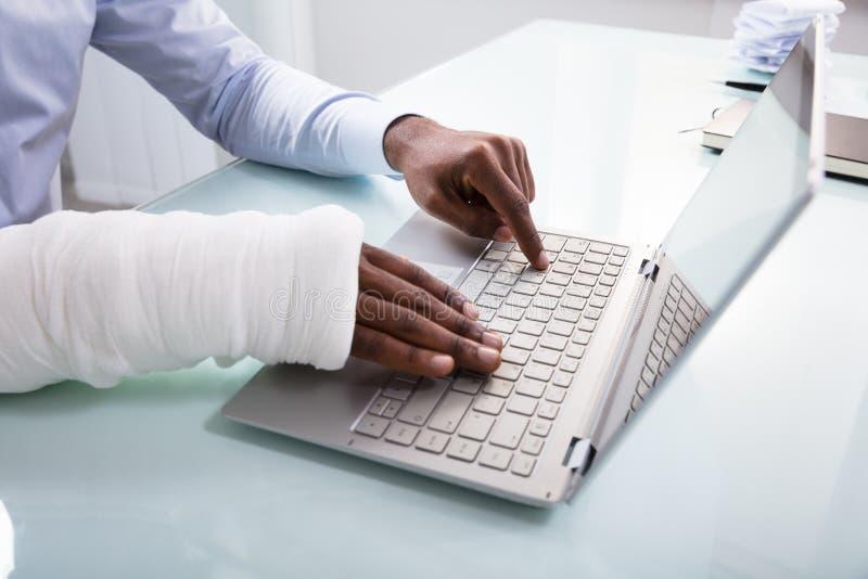 Affärsman With Bandage Hand som använder bärbara datorn arkivfoton
