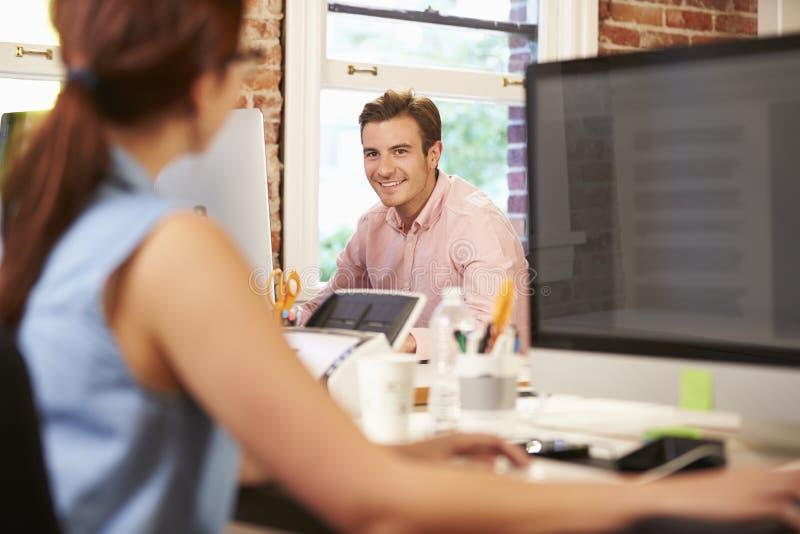 Affärsman And Businesswoman Working på skrivbord i regeringsställning arkivfoton