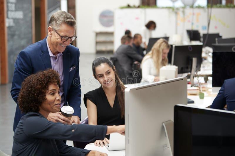 Affärsman And Businesswomen Working på datoren på skrivbordet i öppet plankontor fotografering för bildbyråer
