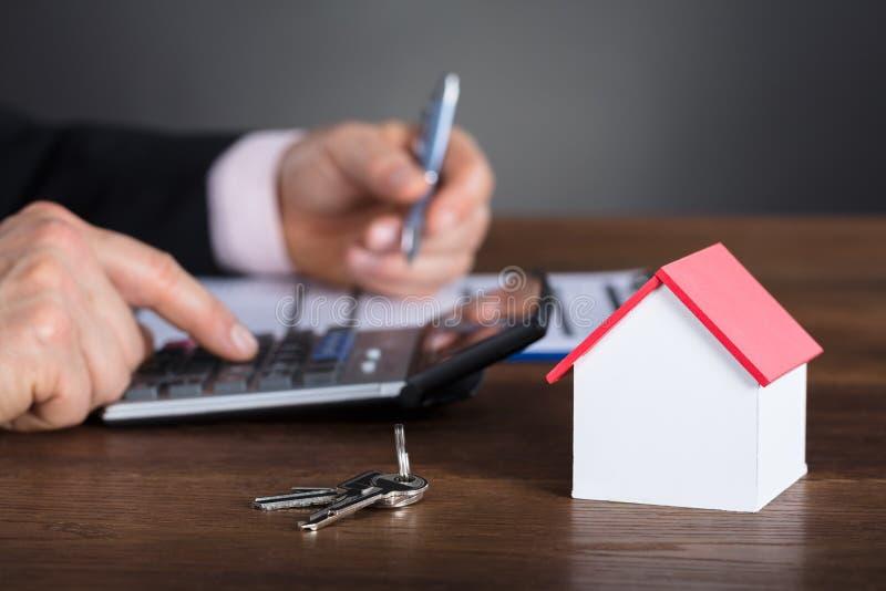 Affärsman Calculating House Costs som använder räknemaskinen royaltyfri foto