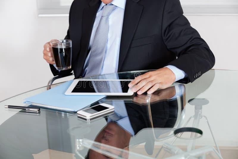Affärsman With Coffee Cup som använder den Digital minnestavlan royaltyfri fotografi