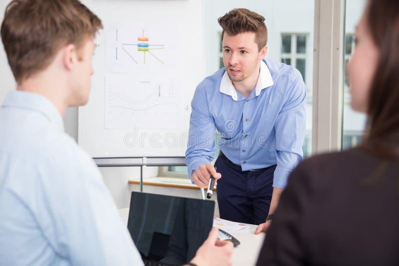 Affärsman Communicating With Colleagues i möte på kontoret royaltyfri bild