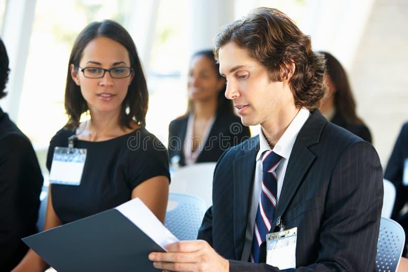 Affärsman Discussing Conference Document med kollegan arkivbild