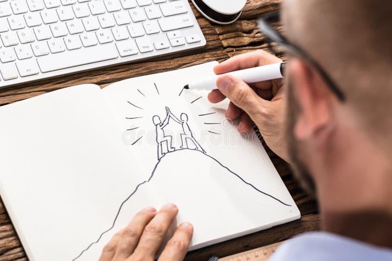 Affärsman Drawing The Figures som ger höjdpunkt fem på anteckningsboken arkivbilder