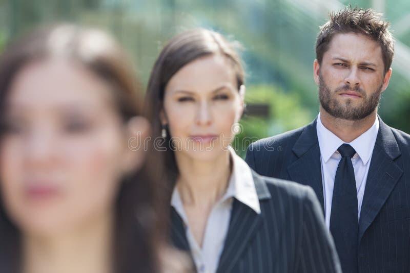 Affärsman för affärsman i linje bak affärskvinnor arkivfoto