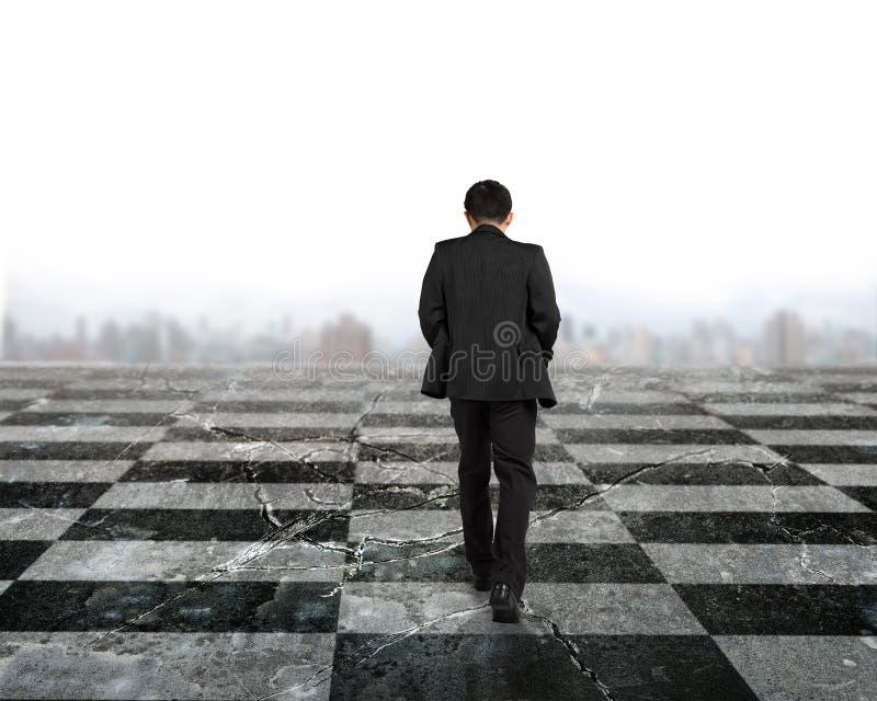 Affärsman för bakre sikt som går på schackbrädet royaltyfria bilder