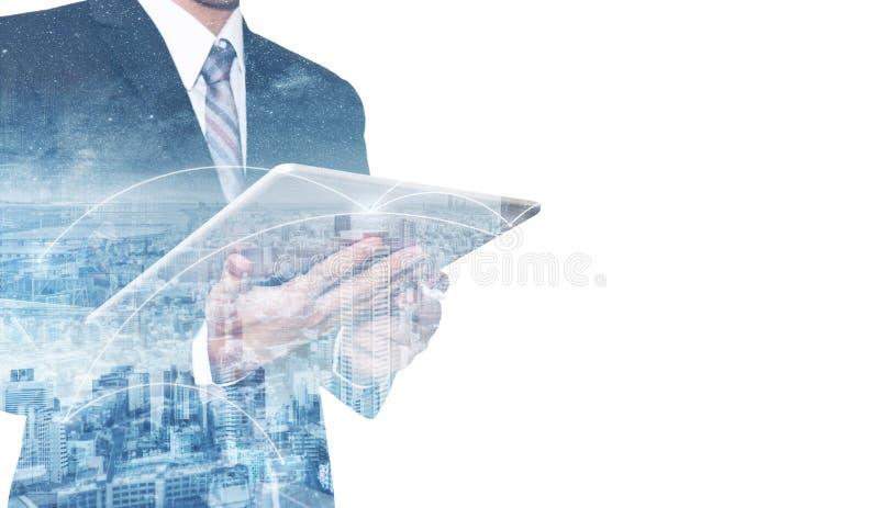 Affärsman för dubbel exponering som använder den digitala minnestavlan och cityscape Affärsnätverk och kommunikationsteknologi royaltyfri bild