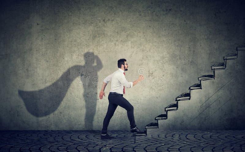 Affärsman för toppen hjälte som kliver upp på trappa som klättrar till framgång arkivbilder