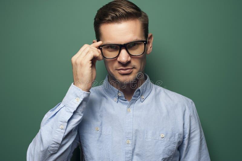 Affärsman för ung man i en blå skjorta och stilfulla exponeringsglas fotografering för bildbyråer