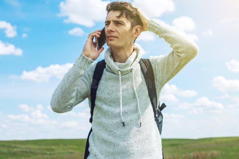 Affärsman för ung man som talar på mobiltelefonen utanför på ett gräsfält arkivbild