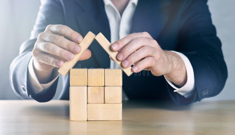 Affärsman, fastighetsmäklare, försäkringmedel eller arkitekt som ordnar och rymmer det skyddande taket över huset som göras från  arkivfoton