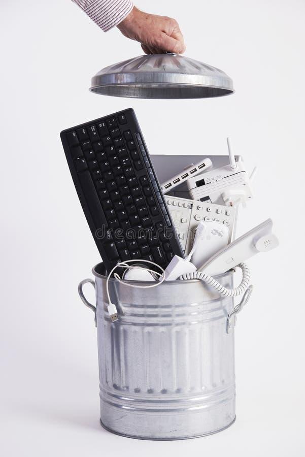 Affärsman Filling Garbage Can med föråldrad kontorsutrustning royaltyfri bild