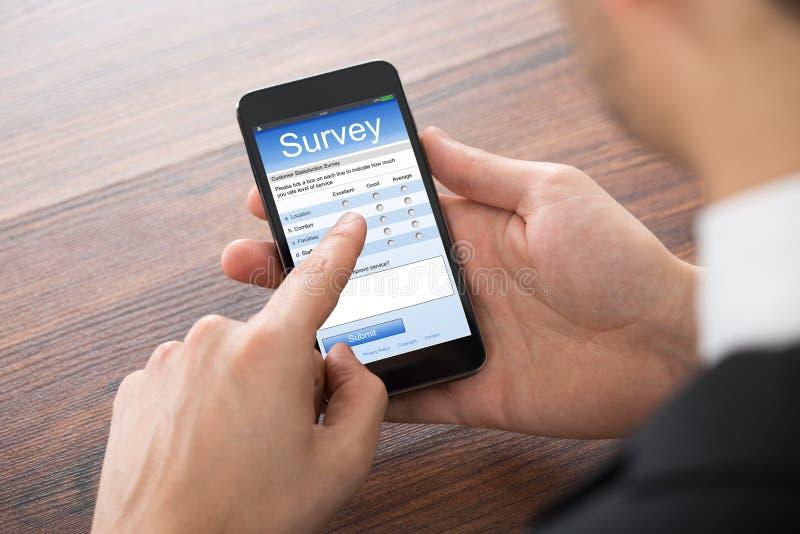 Affärsman Filling Online Survey på mobiltelefonen arkivfoto