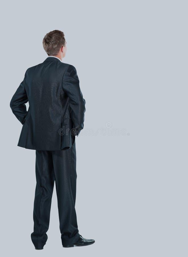 Affärsman från baksidan - se något över en vit bakgrund royaltyfri fotografi