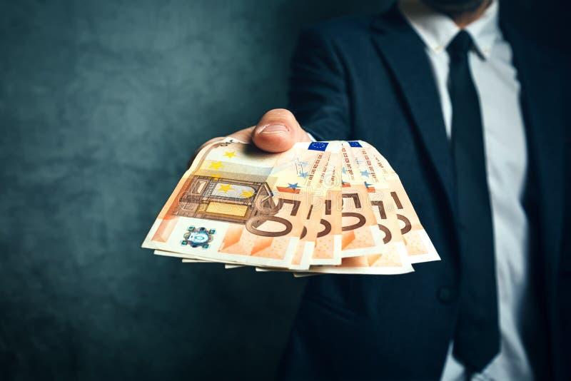 Affärsman från erbjudande pengarlån för bank i eurosedlar arkivbilder